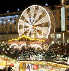 Riesenrad in Bewegung - Nachtaufnahme, Lichtspiel - Striezelmarkt in Dresden, weihnachtlich geschmückte Buden.