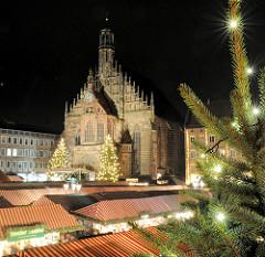 Stoffdächer des Nürnberger Weihnachtsmarkt an der spätgotischen Frauenkirche - Tannenbaum mit Lichtern.
