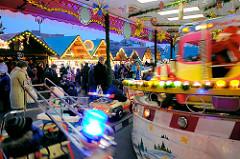 Kinderkarussell in Fahrt auf dem Erfuter Weihnachtsmarkt - beleuchtet Verkaufsbuden.
