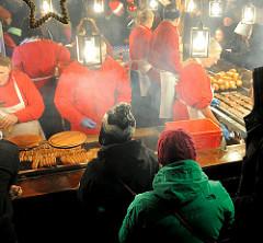 Wurstbude auf dem Nürnberger Weihnachtsmarkt / Christkindlesmarkt - VerkäuferInnen stehen vor dem Bratrost, Dampf steigt auf.