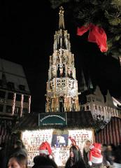 Der 1396 errichtete Schöner Brunnen auf dem Hauptmarkt in Nürnberg - Weihnachtsmarkt - Tanne mit roter Schleife.