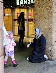 Ein Kind in modischem Rosa gekleidet beobachtet eine Bettlerin am Eingang eines Kaufhauses in Nürnberg.
