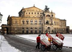 Historische Architektur Dresdens - Semperoper am Theaterplatz; zweirädrige Karren der Dresdner Stadtrundfahrt werden durch den Schnee zum Arbeitsplatz geschoben.