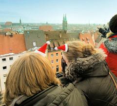 Weihnachtlicher Blick von der Nürnberger Burg auf die Stadt - zwei Touristinnen haben kleine Weihnachtsmützen aufgesetzt.