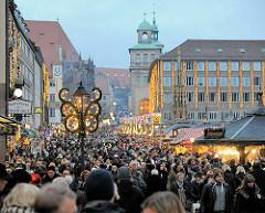 Dichtes Gedränge auf dem Nürnberger Weihnachtsmarkt / Christkindlesmarkt - im Hintergrund die Türme vom 1622 fertig gestellten Wolff'schen Rathausbau.