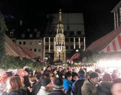 MarktbesucherInnen zwischen Verkaufsständen auf dem Nürnberger Christkindlesmarkt - im Hintergrund der 1396 errichtete Schöner Brunnen