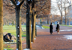 Neustädter Elbufer / Dresden - ein Obdachloser schläft im Schlafsackh auf einer Parkbank - zwei Frauen unterhalten sich; auf dem Weg liegt Schnee.