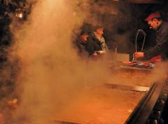 Wurststand auf dem Weihnachtsmarkt in Nürnberg - dichter Rauch, Dampf steigt aus den Kesseln auf.
