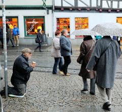 Fussgänger mit Regenschirm im Schmuddelwetter / Schneegriesel am Erfurter Domplatz - Kopfsteinpflaster.