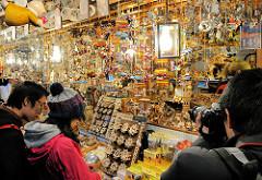 Japanische Touristen auf dem Nürnberger Weihnachtsmarkt / Christkindlesmarkt an einem Stand mit Weihnachtsartikeln.