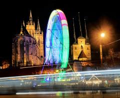 Beleuchtetes Weihnachtsrad / Riesenrad in Bewegung - angestrahlter Erfuter Dom und Serverikirche bei Nacht / Nachtaufnahme.