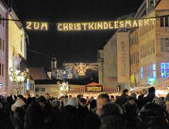 """Leuchtschild """"Zum Christkindlesmarkt"""" - Menschengedränge; im Hintergrund die beleuchtete Bürg von Nürnberg."""
