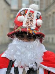 Schwarzer Weihnachtsmann mit weissem Bart und roter Mütze - Strassenrand in Erfurt.