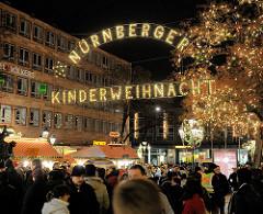 Leuchtschild Nürnberger Kinderweihnacht - MarktbesucherInnen, Baum mit Lichtern geschmückt.