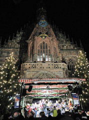 Spätgotische Frauenkirche in Nürnberg - 1352 erbaut; Bühne mit WeihnachtssängerInnen auf dem Nürnberger Christkindlesmarkt.