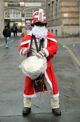 Trommelnder Weihnachtsmann am Wegesrand in Erfurt - weisser Bart - roter Mantel.