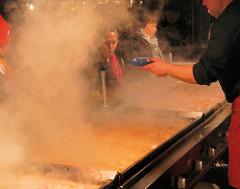 Wurstverkauf auf dem Nürnberger Christkindmarkt / heisser Arbeitsplatz - dichter Rauch steigt auf, die Kunden sind kaum zu erkennen.