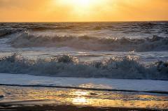 Wellen am Nordseestrand - angestrahlt von der tiefstehenden untergehenden roten Sonne.
