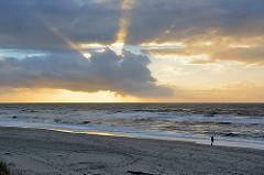 Sonnenuntergang über dem Meer - einsamer Strand an der Nordsee; Spaziergänger am Wasser.