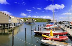 Ferienhäuser auf Stelzen im Wasser mit eigenem Bootsanleger - am Steg liegen Segelschiff, ein Schlauchboot + Ruderboot; Marina Lauterbach Rügen.