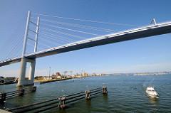 Rügenbrücke über den Strelasund bei Stralsund - Polygon mit Stahlseilen; ein Sportboot fährt unter der Brücke hindurch - Hintergrund der Hafen und die Altstadt von Stralsund