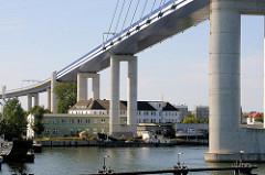 Blick auf die Rügenbrücke bei Stralsund - Y-Stützpaare; Wohnhäuser und Gewerbe unter der Brücke.
