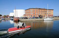 Sportboot in Fahrt - Gründerzeitarchitektur; Teilansicht des Meeresmuseum im Hintergrund.