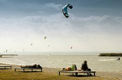 Nachmittag am Strand vom Neusiedler See in Podersdorf - Kitesurfer nutzen den frischen Wind für Ihren Sport - Zuschauer sitzen auf Bänken in der Sonne.