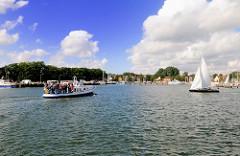 Einfahrt in den Hafen von Lauterbach / Rügen. Eine vollbesetzte Fähre kommt von der Insel Vilm - ein Segelboot kreuzt im Hafen; im Hintergrund die Hafenmole und Hafenpromenade Lauterbachs.
