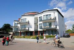 Moderner Neubau, Hafennähe Lauterbach / Rügen. Spaziergänger und Fahrradfahrer auf der Strasse.