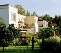 Rechteckige Wohngebäude mit grünen Vorgärten in der Morgensonne; Bilder aus Putbus, Insel Rügen.
