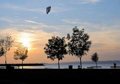 Abendlicht am Neusiedler See am Ufer bei Podersdorf - ein Kitesurfer surft in der Dämmerung auf dem See.