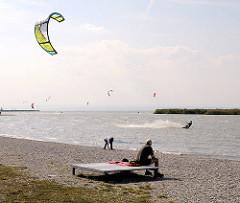 Strand vom Neusiedler See in Podersdorf - Kitesurfer nutzen den frischen Wind für Ihren Sport - Zuschauer sitzen auf Bänken in der Sonne.