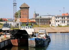 Frachtschiffe am Kai im Straslunder Hafen - im Hintergrund Gewerbegebäude und ein historischer Speicher.