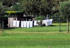 Gewaschene Wäsche auf der Leine in der Sonne auf einer Wiese - Lauterbach / Rügen.