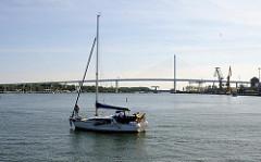 Blick vom Hafen Stralsunds auf die Rügenbrücke - ein Segelschiff fährt unter Motorkraft aus dem Stralsunder Hafen Richtung Ostsee.