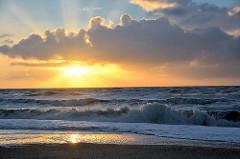 Untergehende Sonne am Meer - Sonneuntergang an der Nordsee; Wellen und Sonnenstrahlen zwischen den Wolken.