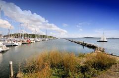 Am Steg liegende Boote und Steinwall - ein Segelschiff läuft aus - Marina Lauterbach / Rügen.