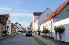 Klassizistische Wohnhäuser mit blühenden Rosensträuchern an der Strasse - Bilder aus Putbus / Rügen.
