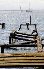 Verfallener Holzsteg, Steganlage des Ferienheims Eisenhüttenkombinats Ost, Eisenhüttenstadt in der Goor - im Hintegrund Segelboote im Greifswalder Bodden vor Lauterbach Rügen.