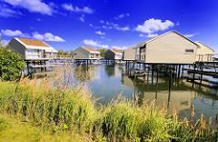 Ferienhäuser auf Stelzen über dem Wasser in der Marina von Lauterbach / Rügen; blauer Himmel, weisse Wolken.
