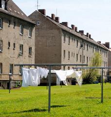 Wäsche trocknen in der Sonne auf der Wiese / Hinterhof mehrstöckiger grobverputzter Wohnblock.