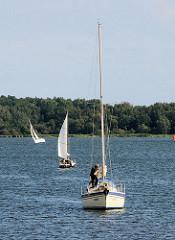 Segelboote laufen in den Hafen von Lauterbach / Rügen ein - im Hintergrund die Insel Vilm.