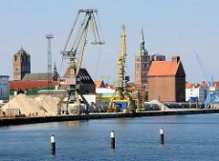 Hafenbereich der Hansestadt Stralsund - Kräne am Kai, Speichergebäude - im Hintergrund Kirchturm der St. Nikolaikirche und  St. Jacobikirche.