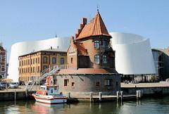 Altes Lotsenhaus im Stralsunder Hafen, dahinter die weisse Architektur des Ozeaneum Stralsund. Der Entwurf für das Meeresmuseum stammt von den Architekten Elke Reichel und Peter Schlaier des Stuttgarter Architekturbüros Behnisch, Behnisch & Partner.