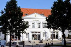 Klassizistisches Gebäude - Hauptstrasse Putbus / Insel Rügen; goldene Schrift Kaufhaus.