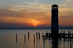 Abendstimmung am Neusiedler See in Österreich - die Sonne geht hinter den Bergen unter - rechts der Leuchtturm von Podersdorf.