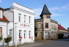 Architektur in der klassizistischen Stadt Putbus / Rügen - weisse Hausfassade, blühende Rosen vor der Fassade - verfallenes Gebäude mit heruntergekommener Fassade - restaurierungsbedürftig.