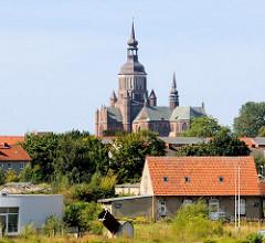 Kirchturm und Kirchenschiff der Stralsunder Marienkirche hinter Dächern von Gewerbehäusern des Stralsunder Hafengebiets.