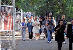 Spazierweg in einer Grünanlage in Krakau - Fotoausstellung mit Papstbildern, Spaziergänger.